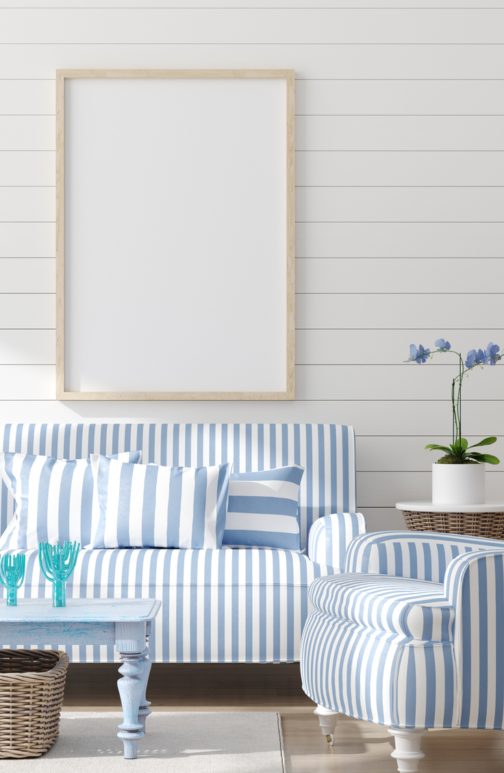 Coastal Home Decor- bright white and blue striped couch and chair with white shiplapped walls behind them. Blue painted coffee table.