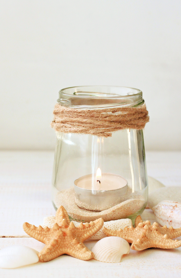 coastal home decor-beach inspired decor. A clear glass jar with just string wrapped around the top with sand inside at the bottom and votive candle. Seashells and shells are scattered around.